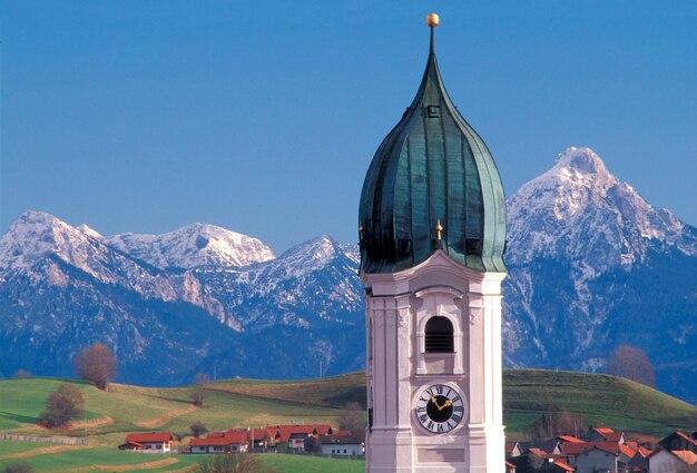 La cupola decorata dell'orologio torreggia sopra il villaggio remoto singolare con le montagne innevate nel fondo