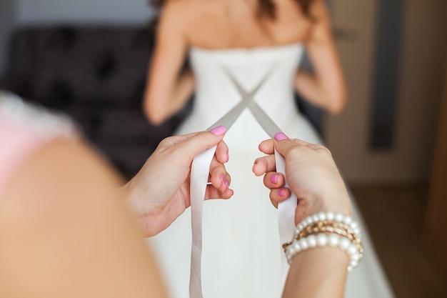 La damigella d'onore fa un nodo a fiocco sul retro dell'abito da sposa