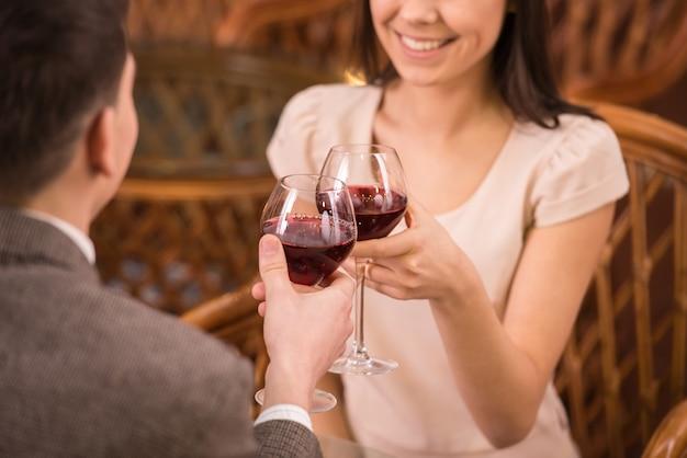 La data romantica delle giovani coppie felici beve il vetro di vino rosso.