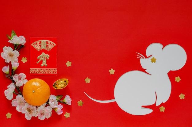 La decorazione cinese del festival del nuovo anno su rosso che ha tagliato nella forma del ratto ha messo sul libro bianco. carattere sul lingotto significa, sul pacchetto di denaro rosso significa grande desiderio.