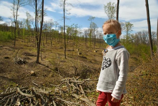 La deforestazione. problemi ecologici del pianeta, quarantena. bambina in una mascherina medica in un sito di deforestazione