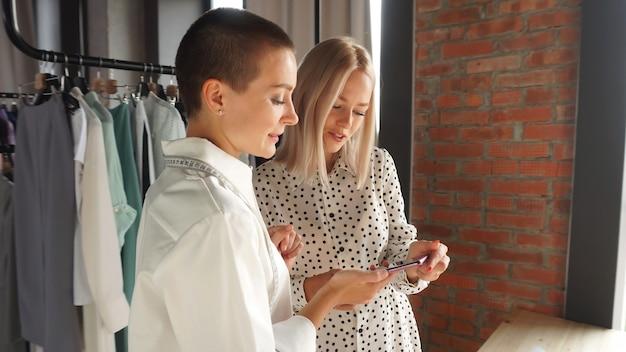 La designer femminile mostra i suoi schizzi di abbigliamento fatti a mano a un bellissimo cliente. il concetto di fashion design