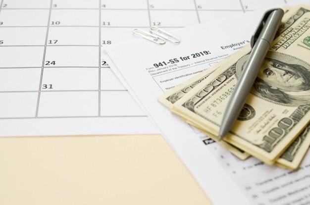 La dichiarazione dei redditi trimestrale trimestrale del datore di lavoro del modulo 941-ss dell'irs è vuota con la penna e molte centinaia di banconote in dollari sulla pagina del calendario