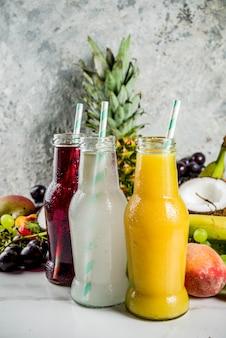 La dieta differente delle vitamine dell'estate di concetto dei frullati dei succhi di frutta con i frutti tropicali e le bacche su un fondo leggero