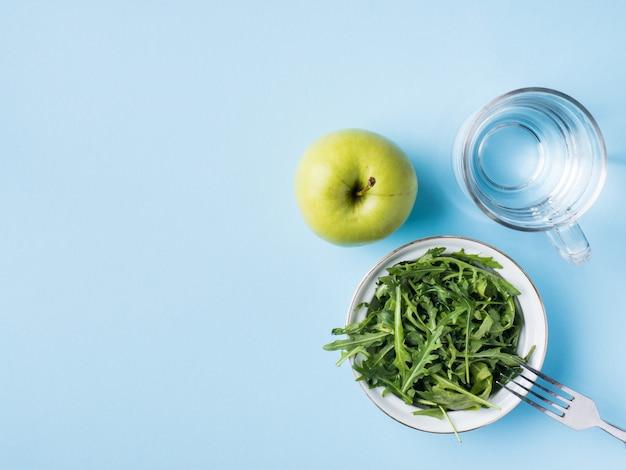 La dieta lascia l'insalata verde apple un bicchiere d'acqua su fondo blu.