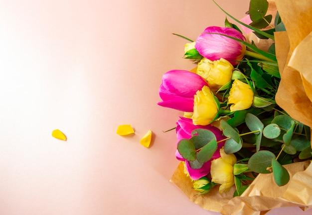 La disposizione creativa di disposizione piana è fatta con i fiori rossi e gialli su fondo rosa.