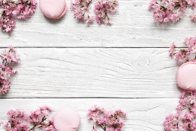 La disposizione creativa fatta con il fiore di ciliegia rosa fiorisce su fondo di legno bianco. disteso. vista dall'alto. cornice di nozze