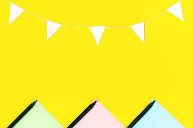 La disposizione della carta colorata, le matite nere e una ghirlanda di bandiere bianche situate sul giallo.