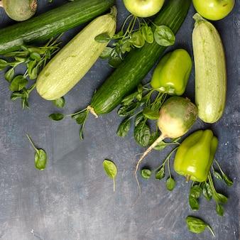 La disposizione delle verdure verdi su un tavolo scuro. set per insalata verde vegana monocromatica.