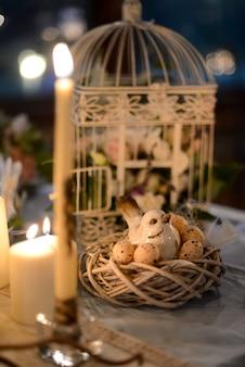 La disposizione floreale nella decorazione di nozze della gabbia un mazzo fiorisce con un uccello e un nido