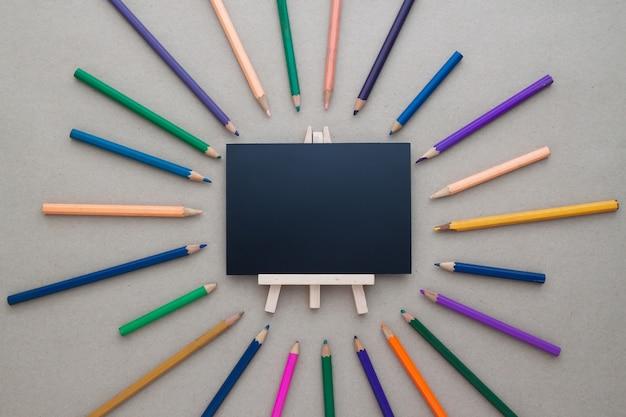 La disposizione piana creativa del bordo nero e le matite di colore, vista superiore con spazio per testo