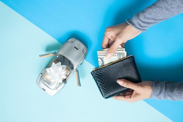 La disposizione piana creativa dell'automobile sportiva con il nastro e la borsa della tenuta della donna e la carta valutano a disposizione