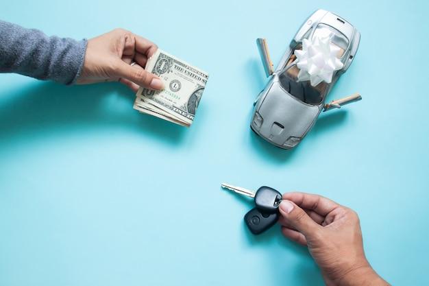 La disposizione piana creativa della mano della donna con valuta di carta e la mano dell'uomo che tiene la chiave dell'automobile
