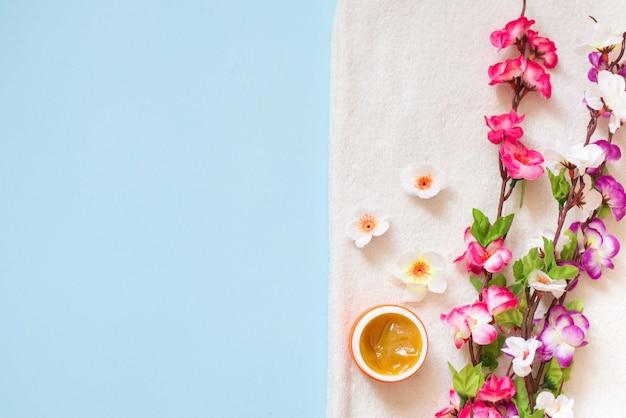 La disposizione piana della crema della stazione termale e colora i fiori sull'asciugamano bianco su fondo blu