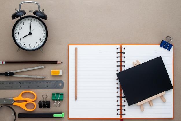 La disposizione piatta creativa di nuovo al concetto della scuola con stazionario sulla scrivania dell'area di lavoro