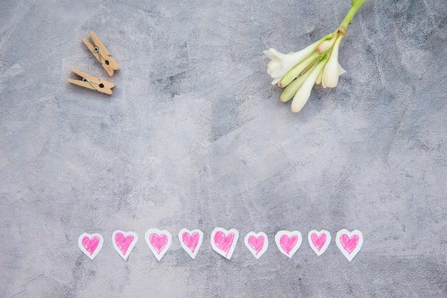 La disposizione piatta del fiore, dei cuori e del legno implora