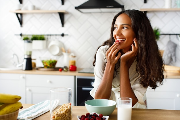 La donna abbastanza africana mangia un lampone prima di una colazione