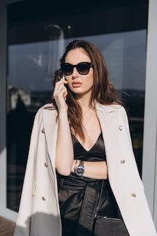La donna abbastanza alla moda di affari sta sul balcone vicino all'ufficio moderno e sta parlando sullo smartphone.