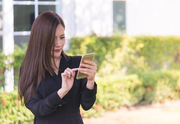 La donna abbastanza asiatica sta mandando un sms sul cellulare nel parco della città