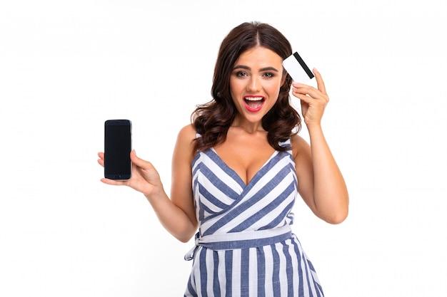 La donna abbastanza caucasica tiene una carta di credito e un telefono cellulare isolati sulla parete bianca