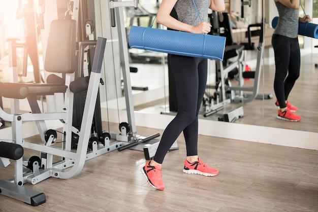 La donna abbastanza giovane di sport è allenamento con la stuoia in palestra, stile di vita sano