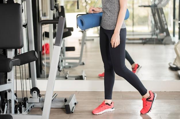 La donna abbastanza giovane di sport è allenamento con la stuoia in palestra