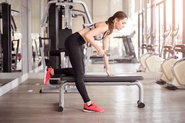 La donna abbastanza giovane di sport è allenamento in palestra