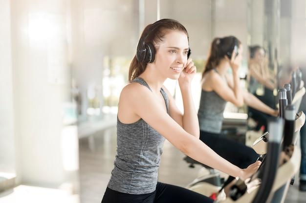 La donna abbastanza giovane di sport è esercizio sulla bicicletta in palestra, stile di vita sano