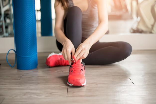La donna abbastanza giovane di sport sta legando le sue scarpe da tennis in palestra, stile di vita sano