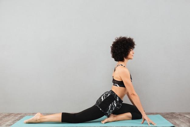 La donna abbastanza riccia di forma fisica fa gli esercizi di yoga di sport