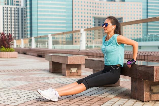 La donna adatta che fa il banco del tricipite si tuffa l'esercizio mentre ascolta la musica in cuffie. ragazza fitness lavorando in città