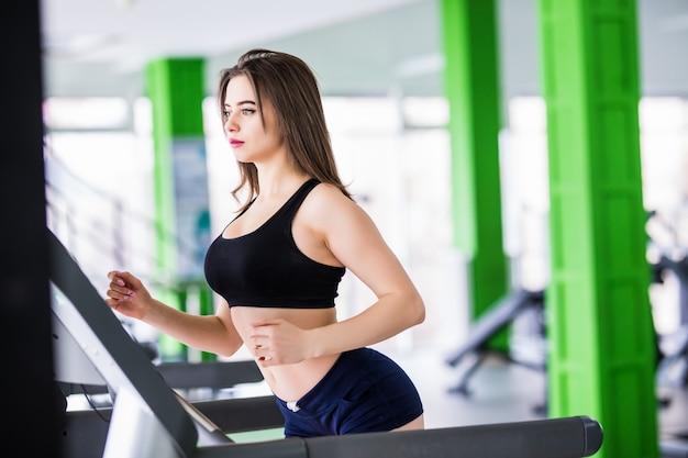 La donna adatta corre sul simulatore di sport nel moderno centro fitness vestito in abiti sportivi neri