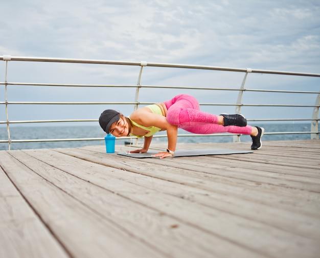 La donna adatta dei giovani in abiti sportivi e la protezione che fanno l'yoga si esercita sulla spiaggia di mattina
