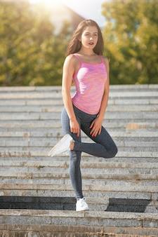 La donna adatta di forma fisica che fa l'allungamento si esercita all'aperto al parco