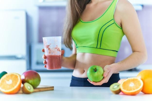 La donna adatta in abiti sportivi beve un frullato di frutta fresca per perdere peso. bevande dietetiche con vitamine per un'alimentazione sana