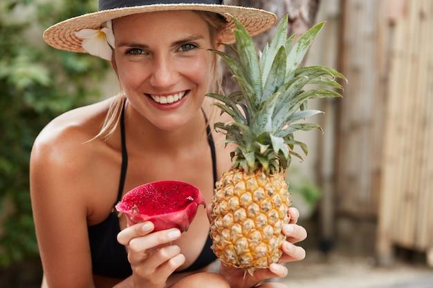 La donna adorabile allegra in cappello di paglia gode delle vacanze estive sulla spiaggia tropicale, tiene l'ananas esotico e la frutta del drago