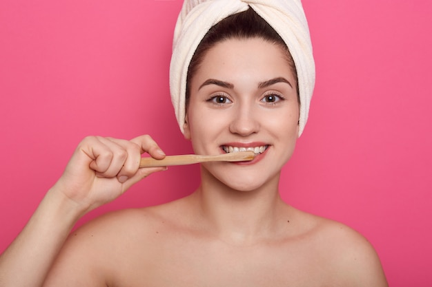 La donna adorabile felice con l'asciugamano bianco sulla sua testa che fa le procedure di mattina in bagno, signora con pelle pulita fresca esamina la macchina fotografica mentre si lava i denti.