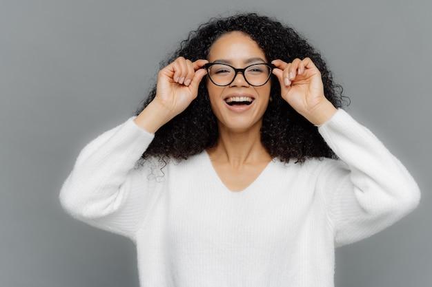 La donna adorabile ottimista osserva felicemente attraverso gli occhiali, tiene le mani sul bordo degli occhiali