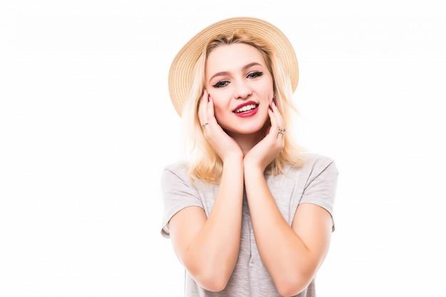 La donna adorabile tiene le sue braccia sotto il suo mento sulla parete bianca