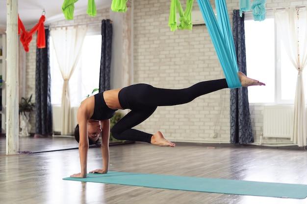 La donna adulta pratica yoga anti-gravità