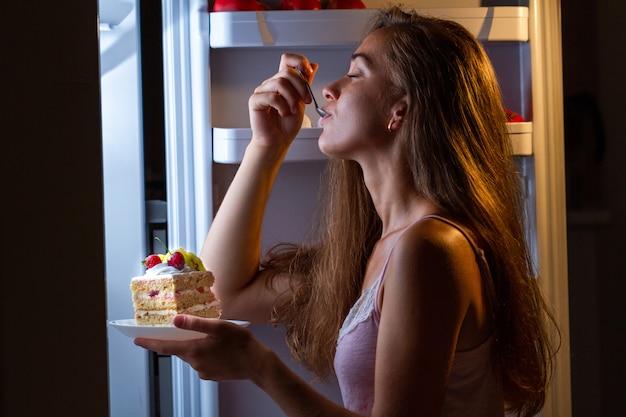 La donna affamata in pigiama gode della torta dolce di notte vicino al frigorifero. interrompere la dieta e guadagnare chili in più a causa di carboidrati e cibo malsano