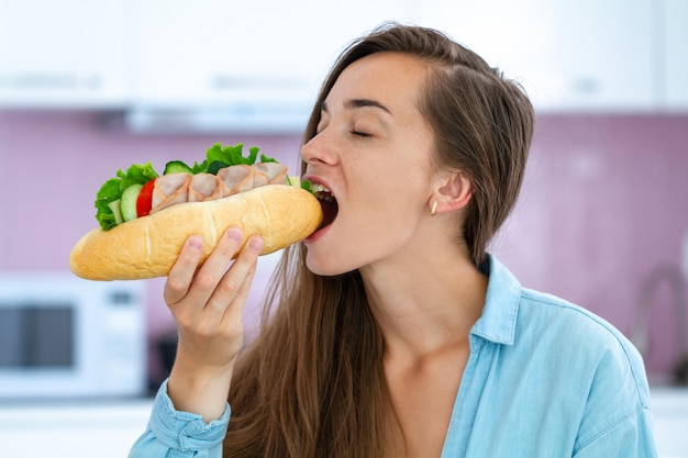 La donna affamata mangia il panino fatto in casa. dipendenza da cibo. ghiottoneria e sovrappeso a causa di un'alimentazione non salutare