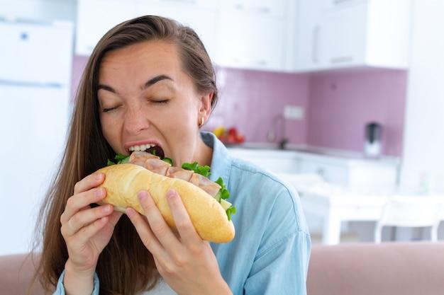 La donna affamata mangia il panino. ghiottoneria e sovrappeso a causa di fast food dannoso e cibo malsano