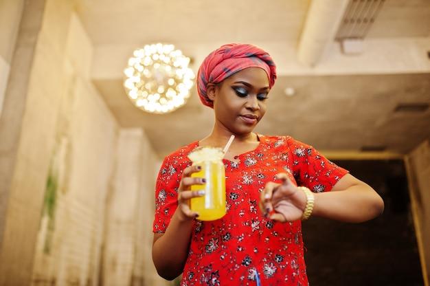 La donna africana alla moda in camicia e cappello rossi ha posato il caffè dell'interno e la limonata bevente dell'ananas