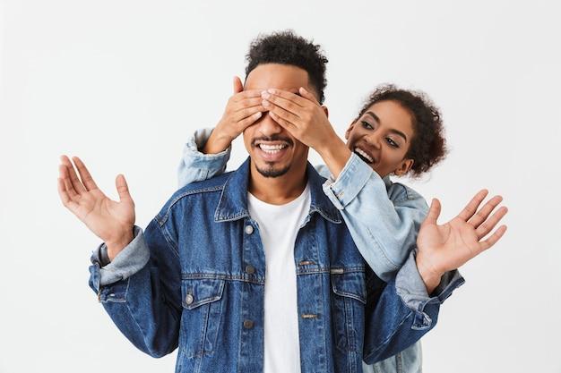 La donna africana allegra che sta dietro il suo ragazzo e copre i suoi occhi sopra la parete grigia
