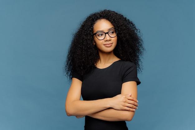 La donna afro tiene le mani incrociate sul petto, si concentra da parte, indossa occhiali trasparenti, maglietta nera casual