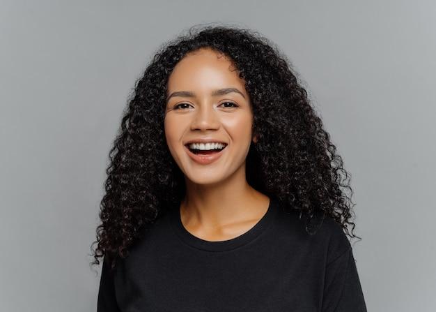 La donna afroamericana dalla pelle scura felice ride positivamente, essendo di buon umore, vestita in abiti casual neri