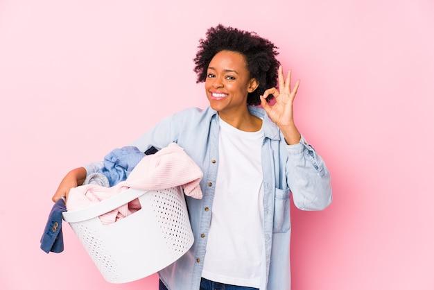 La donna afroamericana di mezza età che fa lavanderia ha isolato allegro e sicuro che mostra gesto giusto.