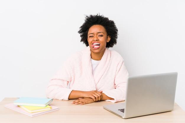 La donna afroamericana di mezza età che lavora a casa ha isolato la lingua attaccante divertente ed amichevole.