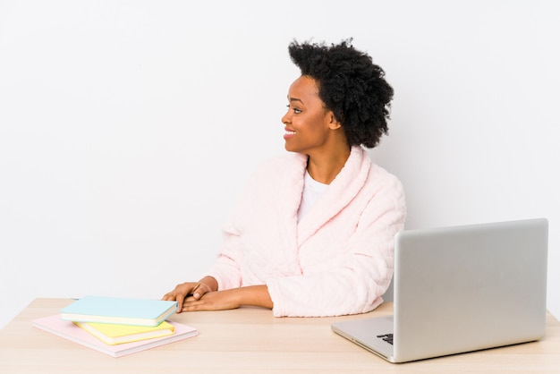 La donna afroamericana di mezza età che lavora a casa ha isolato lo sguardo a sinistra, posa laterale.